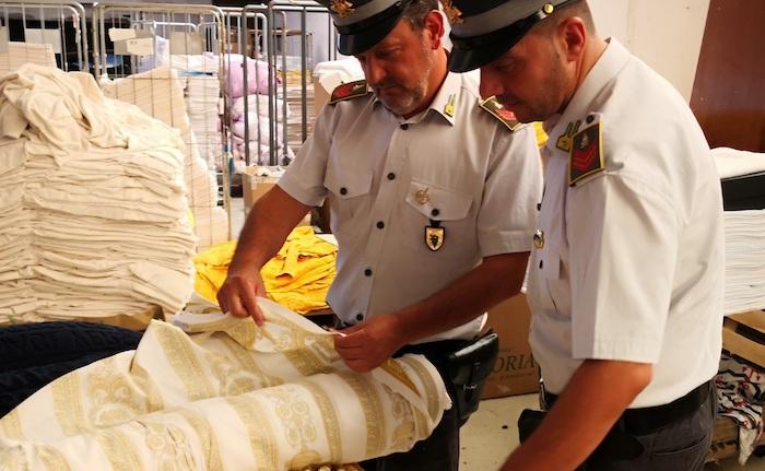 Guardia di Finanza: 8 lavoratori in nero in un laboratorio cinese, 8500 articoli contraffatti